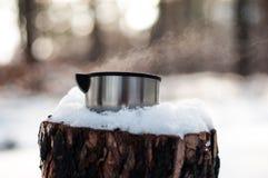 Une tasse de supports chauds de thé sur un tronçon couvert de neige pendant l'hiver, froid, forêt de pin images stock