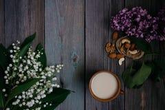 une tasse de thé, écrous, bouquet des lis sur une table en bois image libre de droits