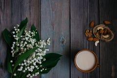 une tasse de thé, écrous, bouquet des lis sur une table en bois photographie stock libre de droits