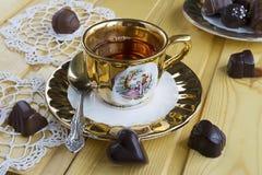 Une tasse de thé avec des bonbons au chocolat sur la table en bois Photographie stock libre de droits