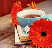 Une tasse de thé avec des fleurs et des livres de gerbera Images libres de droits