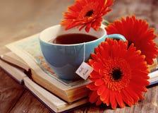 Une tasse de thé avec des fleurs et des livres de gerbera Photos stock