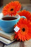 Une tasse de thé avec des fleurs et des livres de gerbera Photo libre de droits