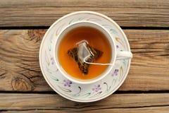 Une tasse de thé avec un sachet à thé de pyramide Photo libre de droits