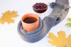 Une tasse de thé chaud avec de la confiture de framboise enveloppée dans une écharpe sur un fond blanc Image stock