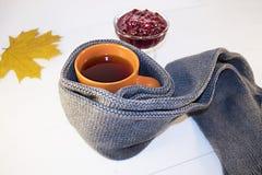 Une tasse de thé chaud avec de la confiture de framboise enveloppée dans une écharpe sur un fond blanc Photo stock