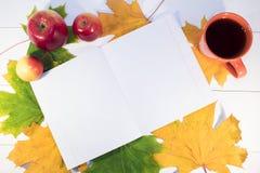 Une tasse de thé chaud d'un carnet et les pommes rouges se trouvent Photo libre de droits