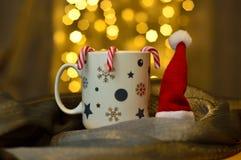Une tasse de thé chaud dans la version de Noël avec le chapeau des cannes du père noël et de sucrerie Photographie stock libre de droits