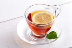 Une tasse de thé chaud de citron avec la tranche de citron et le citron poussent des feuilles Photo stock