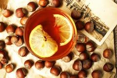 Une tasse de thé chaud noir avec le citron, noisette sur un papier beige avec une rétro carte photos stock