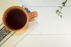 Une tasse de thé chaud se tient sur une serviette sur un fond en bois peint dans le blanc Images stock