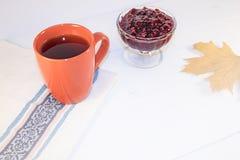 Une tasse de thé chaud se tient sur une serviette sur un fond en bois peint dans le blanc Image stock