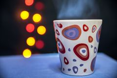 Une tasse de thé chaud sur le fond des lumières images libres de droits