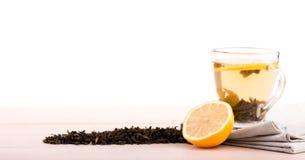 Une tasse de thé complètement de liquide Une tasse en verre sur une table en bois légère Une belle tasse avec le citron et les fe Photographie stock