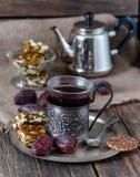 Une tasse de thé, d'écrous rôtis glacés et de dates sur la table du Th Photo stock