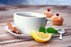 Une tasse de thé, de petit pain et de citron Image stock