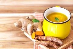 une tasse de thé de safran des indes avec le citron et le gingembre, avantages pour le reduc Images libres de droits