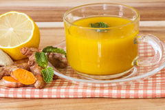 une tasse de thé de safran des indes avec le citron et le gingembre, avantages pour le reduc images stock