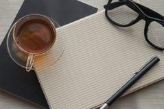 Une tasse de thé est sur le carnet pour le travail images stock