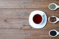 Une tasse de thé et d'épices chauds sur une table en bois Photographie stock libre de droits
