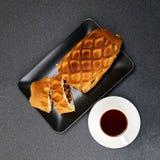 Une tasse de thé et de strudel avec les pommes et la cannelle Photographie stock libre de droits