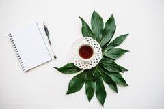 Une tasse de thé de fines herbes ou noir parfumé et délicieux avec des feuilles admirablement étendues à côté de et un carnet pou Photographie stock
