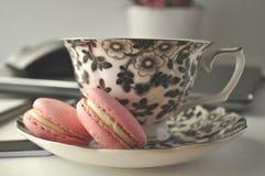 Une tasse de thé florale noire et blanche avec les macarons français roses sur une table avec l'ordinateur portable et une souris Images libres de droits