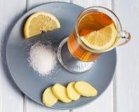 Une tasse de thé de gingembre avec le citron sur un fond en bois Photo libre de droits