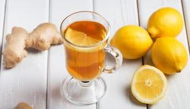 Une tasse de thé de gingembre avec le citron sur un fond en bois Photographie stock
