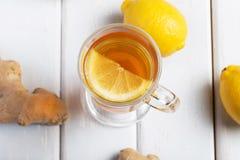 Une tasse de thé de gingembre avec le citron sur un fond en bois Photos stock