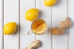 Une tasse de thé de gingembre avec le citron sur un fond en bois Image stock