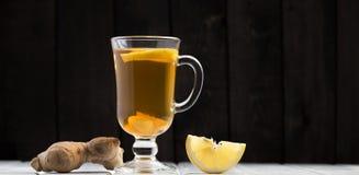 Une tasse de thé de gingembre avec le citron sur un fond en bois Image libre de droits