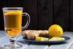 Une tasse de thé de gingembre avec le citron sur un fond en bois Photos libres de droits