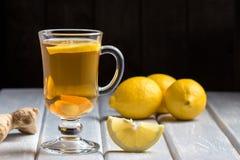 Une tasse de thé de gingembre avec le citron sur un fond en bois Photo stock