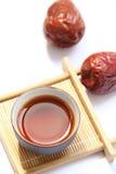 Une tasse de thé noir avec les dates rouges Photographie stock libre de droits