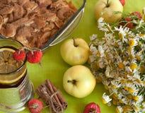 Une tasse de thé noir fort avec une tranche de citron, une tarte aux pommes, un bouquet des camomilles, des bâtons de cannelle, d Photographie stock
