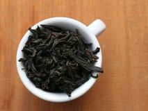 Une tasse de thé sec Thé noir Une tasse de thé image stock