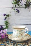 Une tasse de thé sur une table bleue en bois avec un bouquet de fi coloré Photo stock