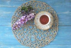 Une tasse de thé sur une table bleue en bois avec un bouquet de fi coloré Image stock