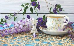 Une tasse de thé sur une table bleue en bois avec un bouquet de fi coloré Image libre de droits