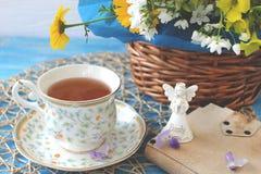 Une tasse de thé sur une table bleue en bois avec un bouquet de fi coloré Photos stock
