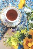 Une tasse de thé sur une table bleue en bois avec un bouquet de fi coloré Photo libre de droits