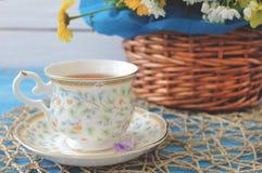 Une tasse de thé sur une table bleue en bois avec un bouquet de fi coloré Photographie stock