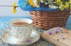 Une tasse de thé sur une table bleue en bois avec un bouquet de fi coloré Photographie stock libre de droits
