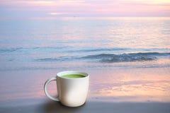 Une tasse de thé vert chaud à la plage photographie stock libre de droits