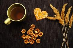 Une tasse de thé vert sur la table avec les épillets et les noix secs sur un fond foncé image stock