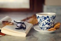 Une tasse de thé vert sur une table de marbre avec un livre ouvert Photo stock