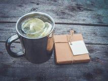 Une tasse en métal avec le thé et le citron à côté d'un paquet de métier avec un label de livre blanc Images libres de droits