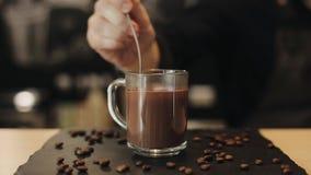 Une tasse en verre avec du chocolat chaud sur la table avec des grains de café Chocolat chaud versant de la cuillère banque de vidéos