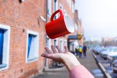 Une tasse fait de la lévitation au-dessus de la main dans un avant d'un fond de ville photographie stock